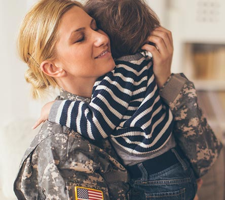 Military mom embracing toddler