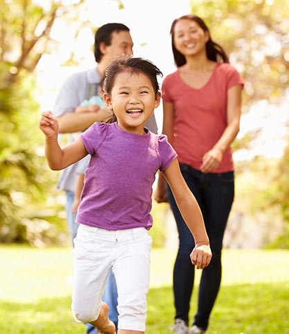 Happy Asian girl running with family